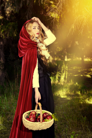 Beautiful blonde woman in  old-fashioned dress and red cloak walking throgh the forest with a basket of apples. Stock fotó