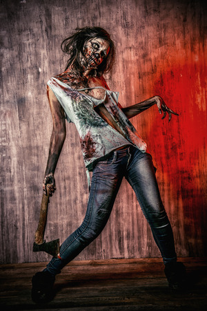 Scary bloody zombie girl with an ax. Halloween. Stock Photo - 35915137