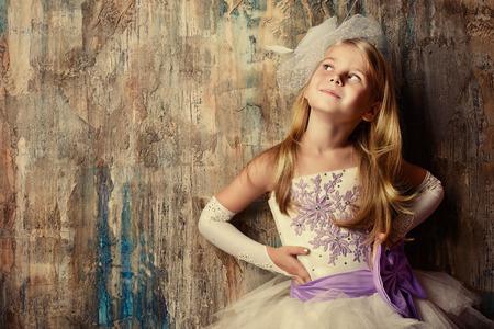 Retrato del arte de un bonito vestido de princesa de la muchacha que lleva. Disparo de moda. Niñez.