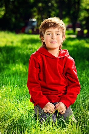 Cute 7 years old boy having fun outdoor. Summer day. Stock Photo