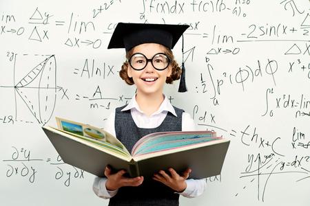 Behoorlijk slim schoolmeisje in grote glazen en academische hoed stands met geopende boek op het schoolbord. Onderwijs.