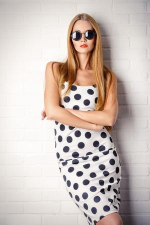 Fashionable lady in polka-dot dress posing near white brick wall. Beauty, fashion concept. Optics. Stockfoto