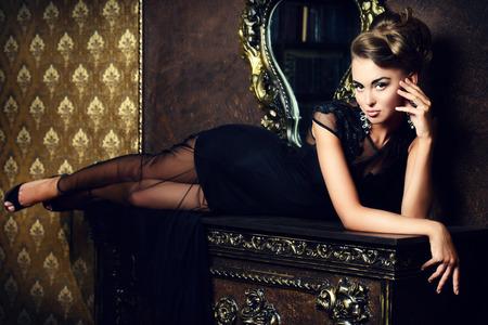 Elegant young woman in black evening dress posing in vintage interior. Fashion shot.