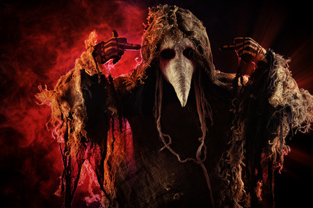 Portrait of a terrible plague doctor with a scythe. Medieval Europe. Horror. Halloween. Stock Photo