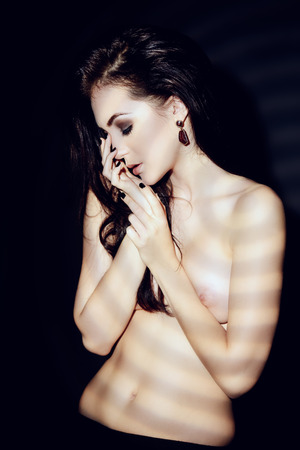 Beautiful slender naked woman posing over black background. Play of light and shadows.