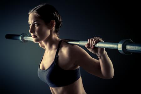 バーベルを演習をやっている美しいスポーツマン体型と強力な若い女性。フィットネス、ボディービル。ヘルスケア。