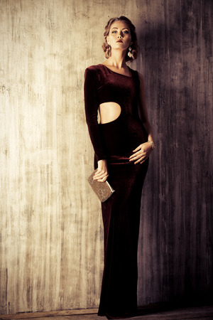 魅力的な若い女性の優雅なイブニング ドレス、美しいヘアスタイルを着ています。ジュエリー。ファッションを撮影しました。完全な長さの肖像画 写真素材
