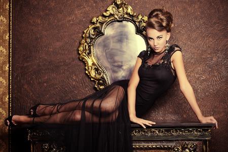 ビンテージ インテリアでポーズをとって黒いイブニング ドレスでエレガントな若い女性