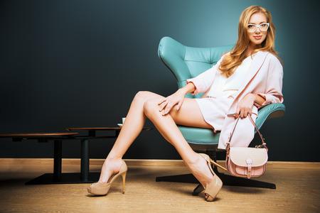Ritratto di un modello alla moda bella seduta su una sedia in stile Art Nouveau. Interni, mobili. Archivio Fotografico - 36682537
