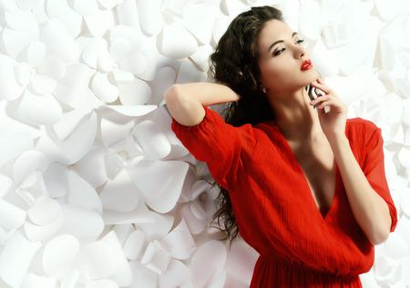 Prachtige mode-model in heldere rode jurk op achtergrond van witte papieren bloemen. Beauty, fashion. Liefde concept. Stockfoto