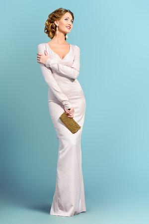 Full length Portret van een mooie vrouw in elegante avondjurk poseren over grijze achtergrond. Fashion schot. Kapsel.