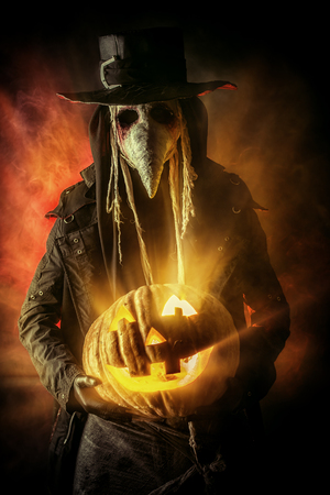 Frightening plague doctor stands with a pumpkin Stock Photo
