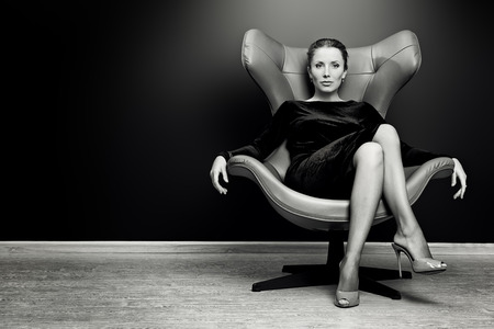 Black-and-white portrait of a stunning fashionable model sitting in a chair in Art Nouveau style