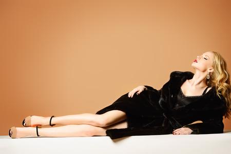 Mujer rubia hermosa que desgasta el abrigo de piel de visón. Moda, belleza. El estilo de vida de lujo. Estudio de disparo.