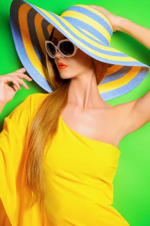 Mooie modieuze dame die fel gele jurk over groene achtergrond