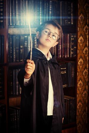 Een jongen staat met toverstaf in de bibliotheek door de boekenkast met vele oude boeken Stockfoto