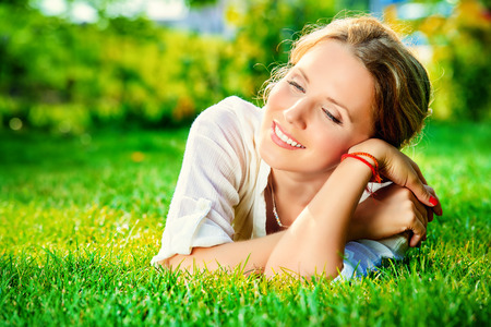 Close-up portrait of a beautiful smiling woman lying on a grass outdoor. She is absolutely happy. 版權商用圖片