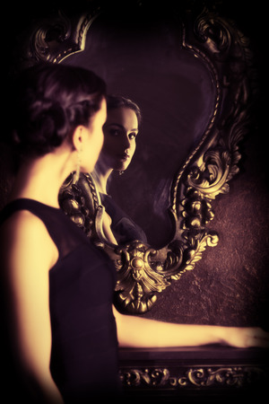 Beautiful elegant lady stands by the mirror in vintage interior. Fashion shot. Stock Photo