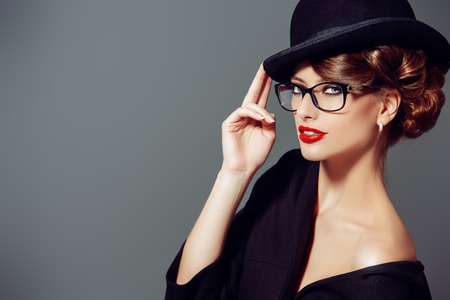Beautiful woman wearing glasses and bowler hat. Retro style. Beauty, fashion. Make-up. Optics, eyewear. Stock Photo