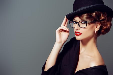 Mooie vrouw draagt een bril en bolhoed. Retro stijl. Schoonheid, mode. Bedenken. Optics, brillen.