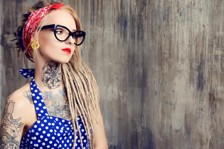 Close-up portrait d'une jeune fille de pin-up moderne vêtu de la robe à pois à l'ancienne et des spectacles et des dreadlocks modernes. tir de mode. Tattoo. Banque d'images - 37229253
