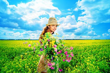Felice giovane donna in piedi in un campo di fiori gialli in fiore. Estate.