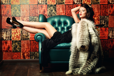 Beautiful charming woman in elegant evening dress and fur coat in a classic interior. Fashion, glamour.