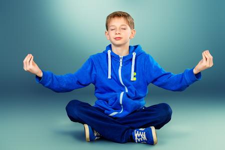 かわいい十代の少年もヨガのポーズで床に座って、瞑想します。スタジオ撮影します。