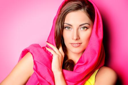 핑크 배경 위에 밝은 진홍의 머리 스카프에 긍정적 인 젊은 여자의 아름다움 초상화. 뷰티, 패션. 화장품. 스톡 콘텐츠