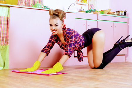 Pretty sexy pin-up girl cleans her glamorous pink kitchen. Retro style. Fashion. Stok Fotoğraf