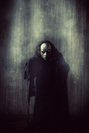 Enge man in ijzeren masker en zwart gewaad. Fantasie. Halloween.