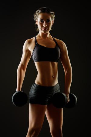 Joven esbelta con hermosas haciendo ejercicios de cuerpo atlético con pesas. Fitness, culturismo. Cuidado de la salud.