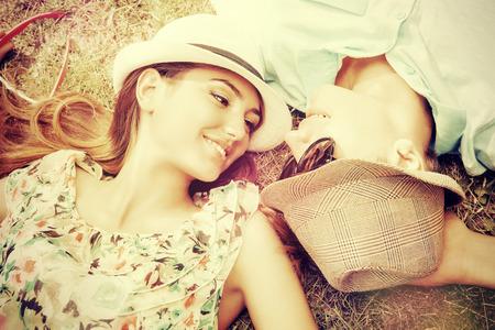 여름 공원에서 잔디밭에 편안한 행복 한 젊은 커플. 개념을 사랑 해요. 휴가.