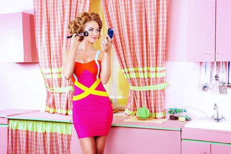 Mujer bonita que hace maquillaje en su cocina rosa glamour en casa. Belleza, la moda.