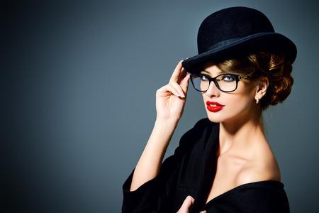 Beautiful woman wearing glasses and bowler hat. Retro style. Beauty, fashion. Make-up. Optics, eyewear.
