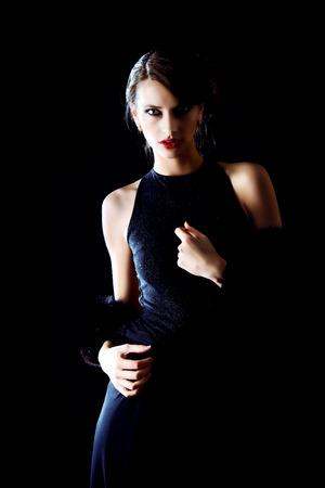 魅力的な若い女性がポーズを黒の背景に黒のイブニング ドレスを着ています。高級。美容、ファッション。メイク。