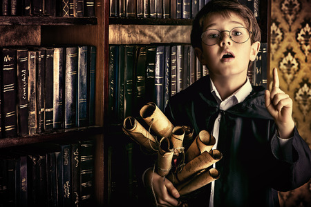A boy stands in the library by the bookshelves with many old books and holds old manuscripts. Educational concept. Science. Vintage style. Zdjęcie Seryjne