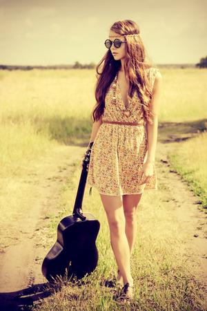ロマンチックな女の子彼女のギターと一緒に旅行します。夏。ヒッピー スタイル。