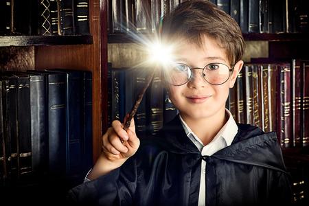 Chłopiec stoi z różdżką w bibliotece przez półki z wielu starych książek. Bajki. Zabytkowy styl.