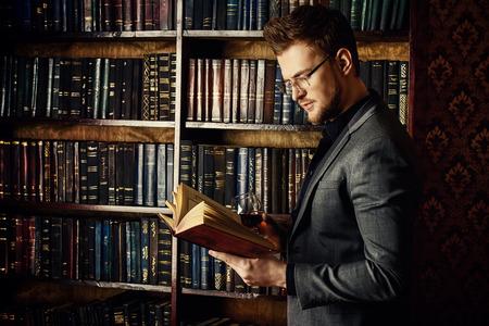 ハンサムな身なりの男は、古典的なインテリアで部屋の本棚で立っています。ファッション。