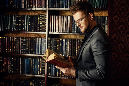Handsome well-dressed man stands by bookshelves in a room with classic interior. Fashion. 免版税图像