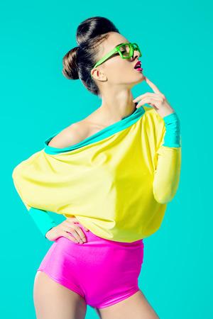 鮮やかな色鮮やかな服を着てポーズ表現のファッションモデル。鮮やかな流行。光学・視力補助用品スタジオ ショットします。