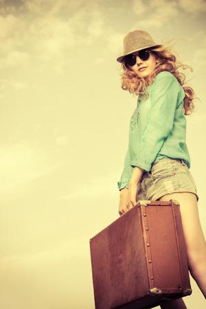 Portrait d'une belle jeune femme avec sa vieille valise contre le ciel bleu. tir de mode.