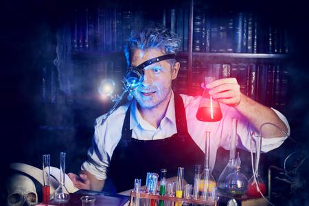 Portret van een gekke middeleeuwse wetenschapper die in zijn laboratorium. Alchemist. Halloween.