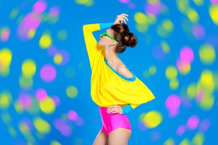 華やかなファッション モデルポーズ鮮やかなカラフルな服やサングラス。鮮やかな流行。光学・視力補助用品スタジオ ショットします。