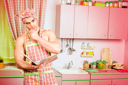 Handsome muscular man in an apron studies a cookbook in the pink kitchen. Love concept. Valentines day. Womens day.