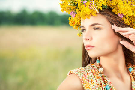 Romantic girl in a wreath of wild flowers in a field. Summer life. Beauty.