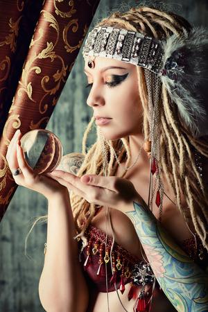 壮大な占い師が水晶玉を保持しています。占い。魔法。ハロウィーン。 写真素材
