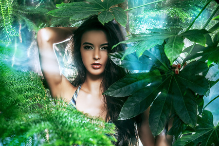 Close-up portrait of a magnificent sexy woman in bikini among tropical plants. Make-up, cosmetics. Beauty, fashion. Spa, healthcare. Tropical vacation.