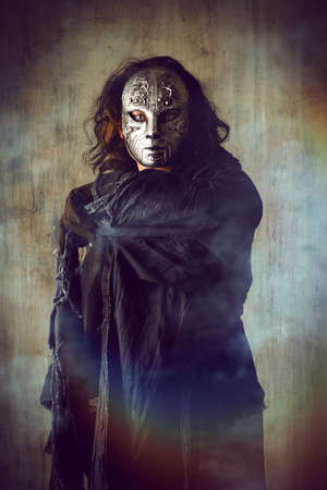 Scary man in iron mask and black robe. Fantasy. Halloween.